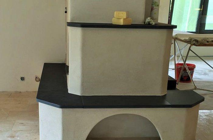 Ein individueller Kachelofen als Kombiofen mit keramischen Zügen sowie ein Olsberg Profi 12 Kachelofeneinsatz 12 kW. Der verputzte Kombiofen verfügt über ein Holzfach und mehreren Ablageflächen aus Naturstein Schiefer.