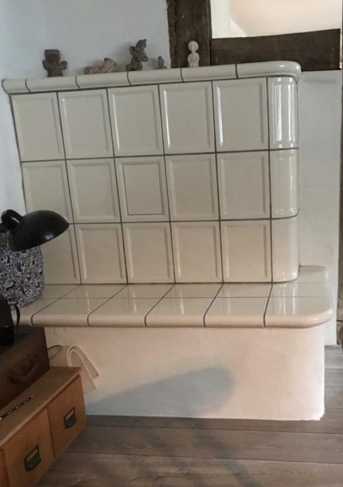 Ein individueller Kachelofen mit beheizter Sitzbank und Holzbank als Raumteiler zwischen Küche und Wohnzimmer, Brennzelle Olsberg Profi 7, 7 kW.  Der Kombi – Kachelofen verkleidet mit Gutbrod Keramik, Farbe weiß und verfügt über mehreren keramischen Zügen.