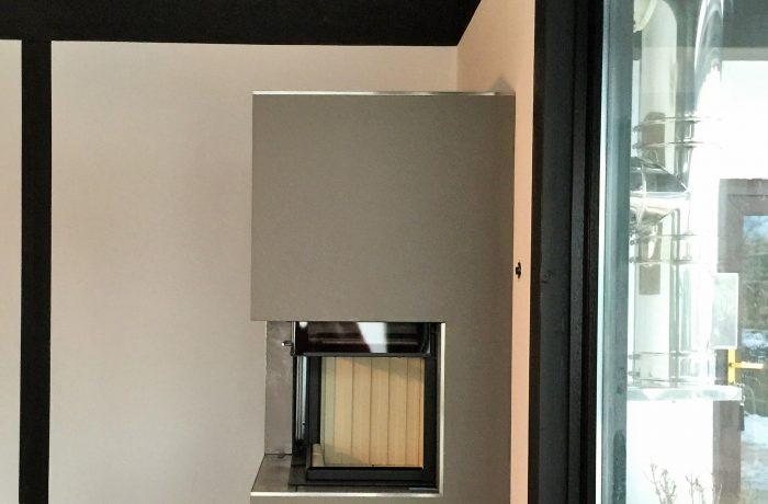 Eine individuelle zweiseitige Kaminanlage mit Spartherm Brennzelle hochschiebbar Varia 2RH.  Der Kamin verfügt über ein Holzfach sowie Edelstahlabschlusskanten. Am Neubau wurde gleichzeitig ein doppelwandiger Edelstahlschornstein montiert.