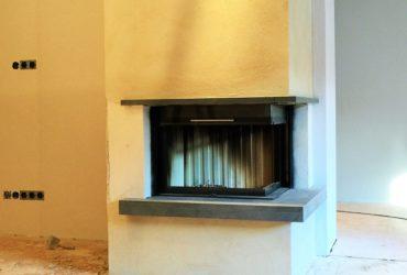 Eine individuelle Gestaltung einer zweiseitigen Kaminanlage mit Spartherm Brennzelle hochschiebbar Varia 2RH 7 kW. Der Kamin ist weiß verputzt und mit einem chinesischen Granit (Naturstein) versehen.