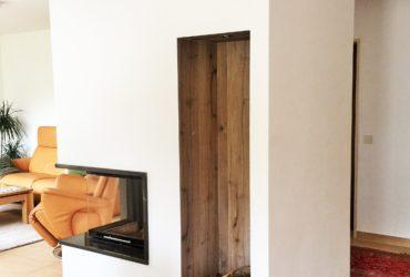 Eine individuelle moderne Gestaltung einer zweiseitigen Eckkamin-Anlage mit Holzfach in Fliesen als Raumteiler zwischen Küche und Wohnzimmer.