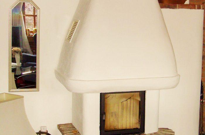 Eine individuelle Gestaltung eines verputzten Kachelofens mit Abbruchsteinen als Plattsims.