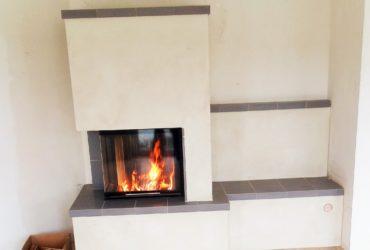 Eine individuelle Gestaltung einer zweiseitigen Kaminanlage mit Spartherm Brennzelle hochschiebbar Varia 2L-50h-4S 7 kW. Der Kamin verfügt über eine Sitzbank in Gutbrod Keramik, Farbe blaugrau.