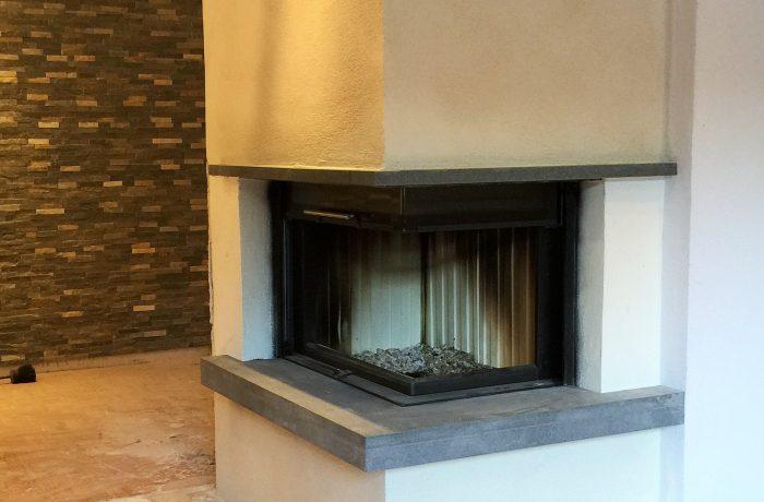 Eine individuelle zweiseitige Eckkamin-Anlage mit schwenkbarer Tür, Spartherm Brennzelle Varia 2R, 11 kW.   Die Kaminanlage ist verputzt und verfügt über eine Sitzbank aus Naturstein, roter Sandstein.