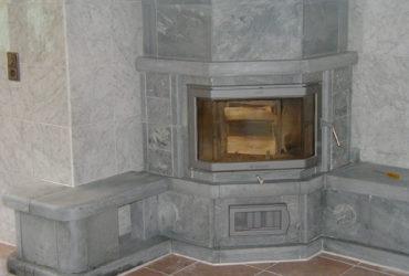 Dieser Ofen schmiegt sich perfekt in Raumecken ein. Die Gestaltung ist klassisch, wobei sich auf beiden Seiten eine kleine Sitzbank dem Ofen anschließt.