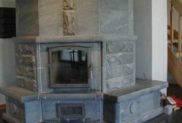Specksteinofen in symmetrischer Form, ideal als Ecklösung und für größere Räume. Im Mittelteil wurde der Speckstein im Look einer Steinmauer gestaltet. Das verleiht ihm einen edlen und erhabenen Touch.